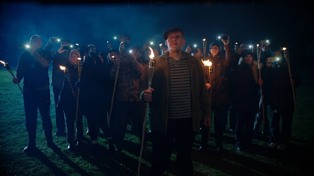 A crowd gathers with torches