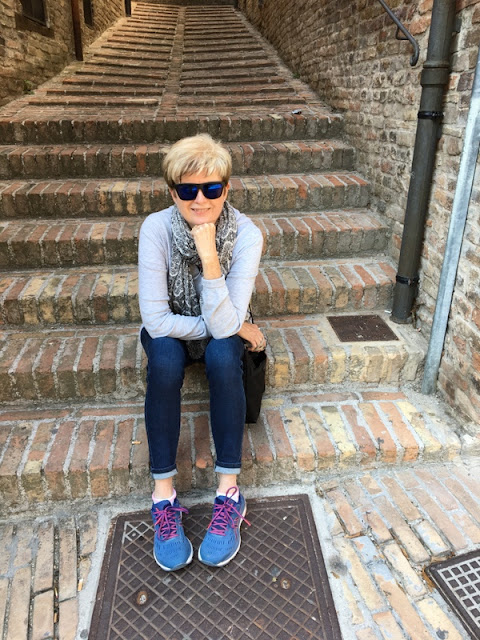 woman sitting on stone steps in Urbino, Italy