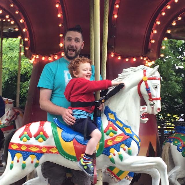 Little boy smiling whilst on a carousel house, being watched over by a smiling daddy