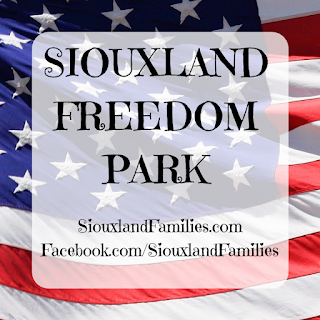 "a close up view of the corner of an American flag is visible in the background. in foreground, the words ""Siouxland Freedom Park"" and ""SiouxlandFamilies.com Facebook.com/SiouxlandFamilies"""