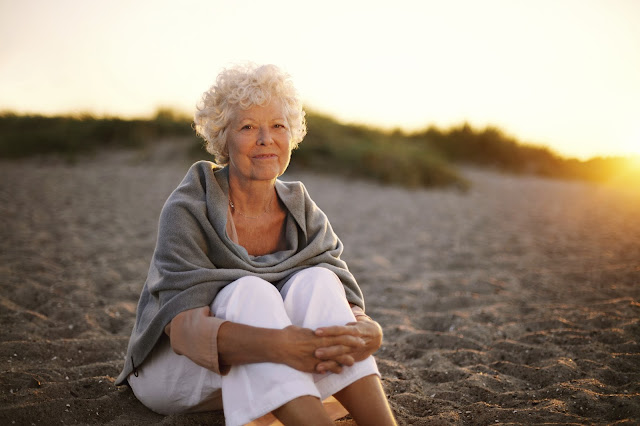 A woman peacefully sitting on the beach