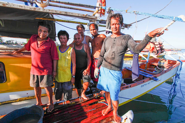After years of driving them away, Chinese coast guards in Panatag Shoal share food with Filipino fishermen
