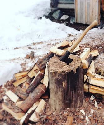 puuvartinen kirves pystyssä puupölkyssä talvella halkoja maassa