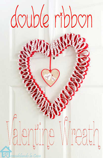 A heart shape valentine's day wreath done with red and white ribbons.