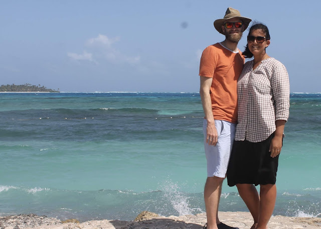 A man and a woman standing in front of the Caribbean Sea on the island of San Andres, Colombia.