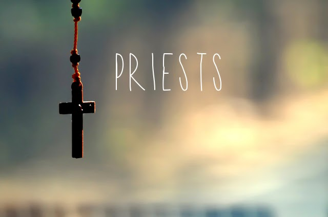 A cross hanging from rosaries with a blurred background. priests is written on the picture.