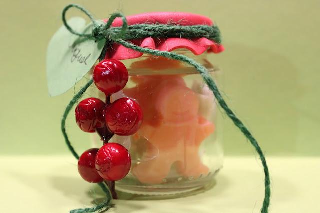 Frasco, decorado com bolas vermelhas de azevinho, com sabonetes em forma de motivos de Natal