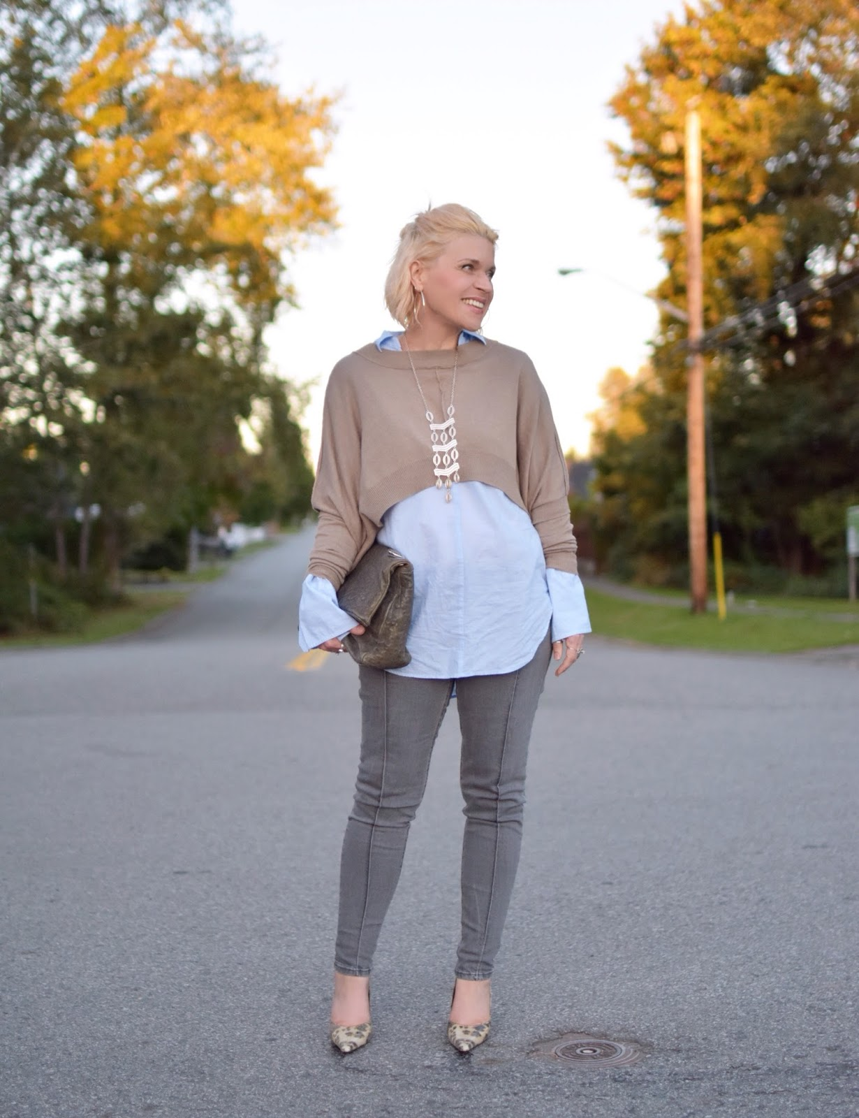 Monika Faulkner styles a drapey shrug with an oversize-cuffed shirt, grey skinny jeans, and reptile-patterned pumps