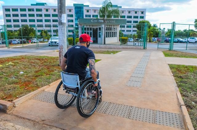 Cadeirante sobe a calçada com acessibilidade perto do hospital