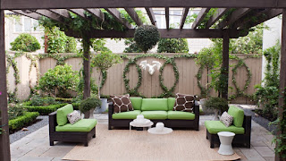 Black couches with lime green cushions under a black perugula in a walled patio area. The are plants in beds along the wall and growing in circles on the wall.