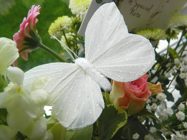A photo of a glittery butterfly pick in a bouquet of flowers