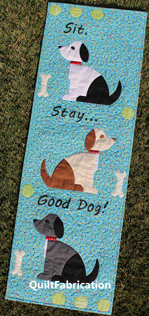 three different colored dogs on an aqua wall hanging
