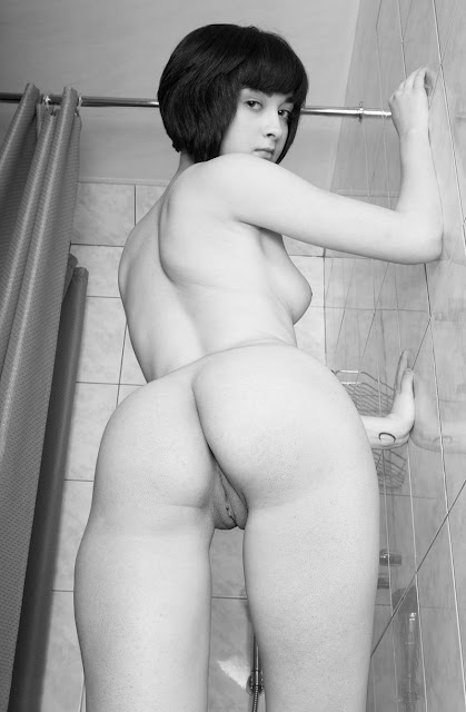 Bild av en sensuell modell i duschen som visar sin rakade bullfitta bakifrån.
