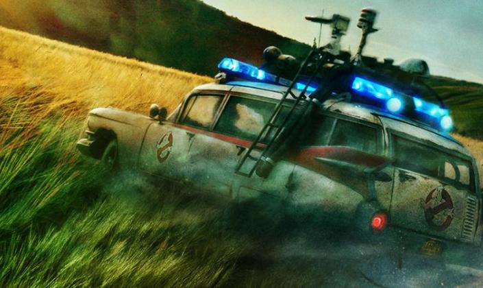 Imagem de capa: um campo de trigo com uma floresta ao fundo e o carro dos Caça-Fantasmas com o símbolo dos Caça-Fantasmas, um fantasmas com um símbolo vermelho de proibido por cima dele e vários radares e e máquinas brilhando uma luz azul por cima do carro.