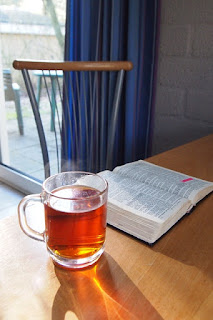 open bible on table with glass tea cup