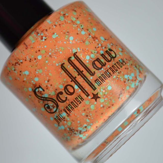 orange nail polish with colorful glitter in a bottle