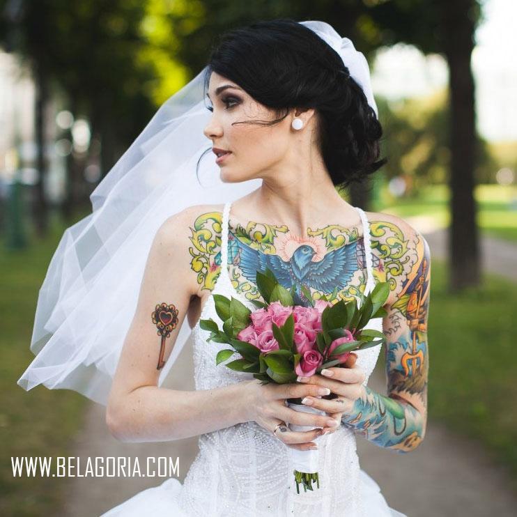 Chica tatuada vestida de novia caminando por una vereda con el ramo en las manos