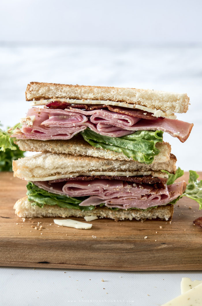 Two ham club sandwich halves stacked on top of one another
