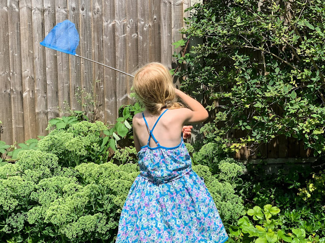 rear view of a 7 year old attempting to catch a butterfly with a net
