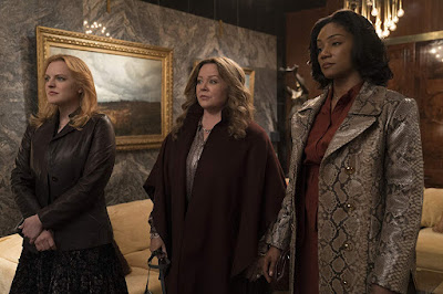 Elisabeth Moss, Melissa McCarthy, and Tiffany Haddish stand their ground in stunning clothing in a movie still for the 2019 drama film The Kitchen