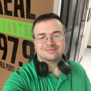 The picture:  a selfie of me, wearing a green shirt, standing before the logo of the radio station I used to work at