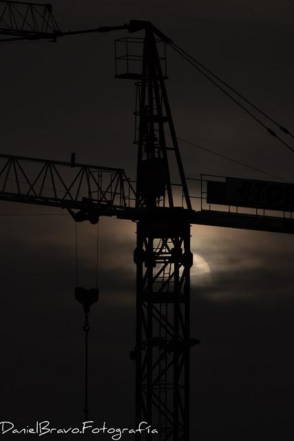 Imagen del primer plano de una grúa de obra a contraluz con el Sol detrás de ella entre nubes