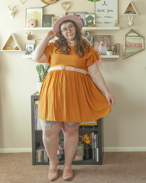 An outfit consisting of a wide brim pastel pink hat, a mustard yellow baby doll dress with flounce sleeves belted with a pastel oink belt and muted pink pointed toe mules.