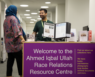 """Image shows the RACE Centre desk which reads """"Welcome to the Ahmed Iqbal Ullah Race Relations Resource Centre""""in large writing. Smaller text reads """"our collections have books, oral histories, photographs, local studies, archival documents, and more"""""""
