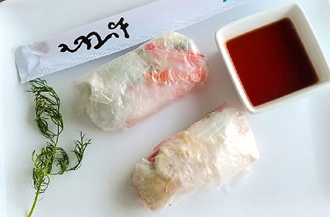 these are rice wrapper rolls with vegetables and meat inside, chopsticks, soy sauce and dill