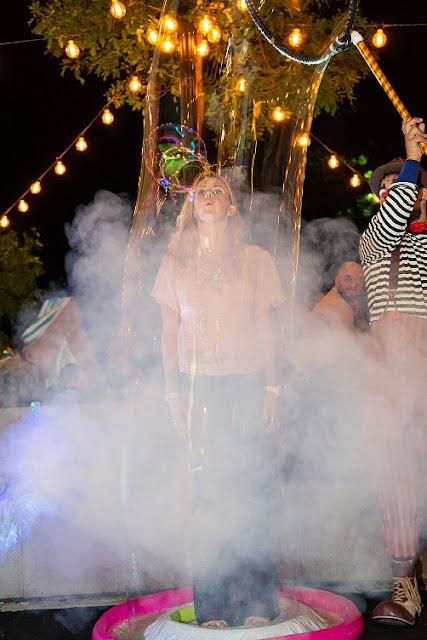 Artista com Bolhas Gigantes faz numero participativo com alguem do público dentro de Bolha de Sabão em evento no Rio.