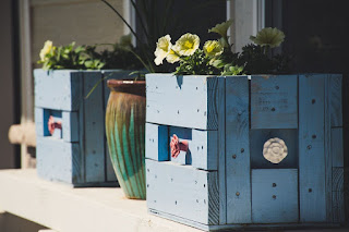Caisses bois bricolées en pots de fleurs.