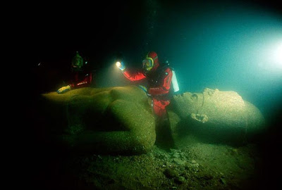 Franck Goddio and divers of his team inspecting the statue of a pharaoh found close to the big temple of sunken Heracleion