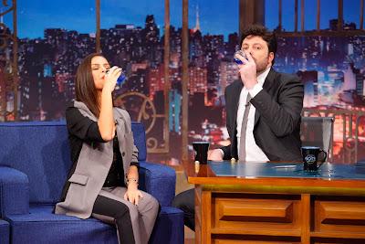 A atriz oferece uma bebida relacionada à série 'O Escolhido' ao apresentador (Crédito: Gabriel Cardoso/SBT)