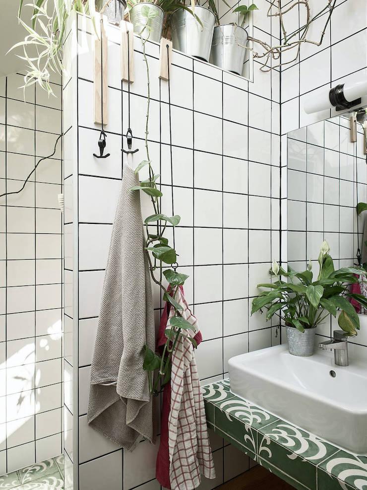 Un ático con una reforma de cocina low cost: baño con azulejos blancos y ducha de obra.