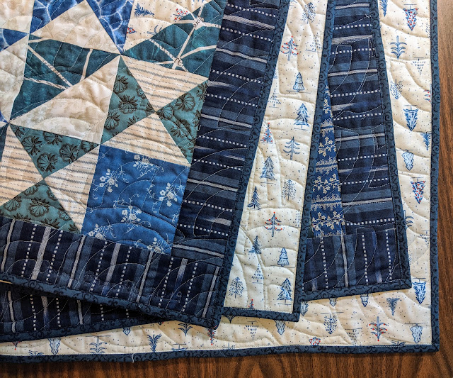 The folded quilt shows part of the front, the back's print of blue pines in the snow, and the dark blue floral binding. The Baptist fan quilting is visible, too.