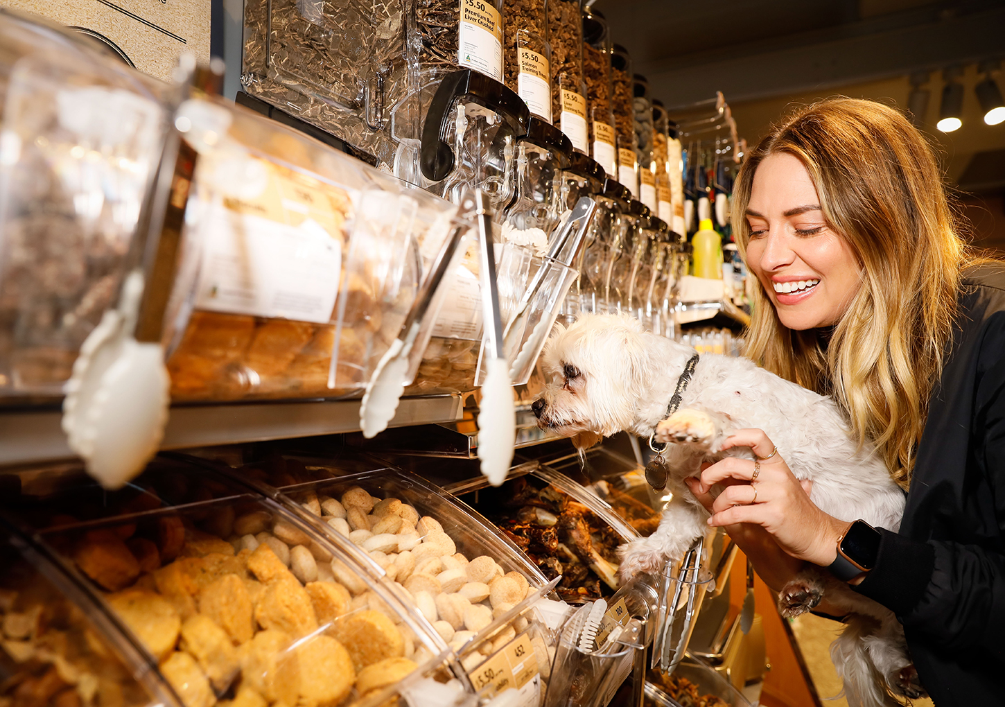 Young woman holds up a Maltese Shih Tzu dog closer to Doggy Treats Bar at Coles Local Rose Bay
