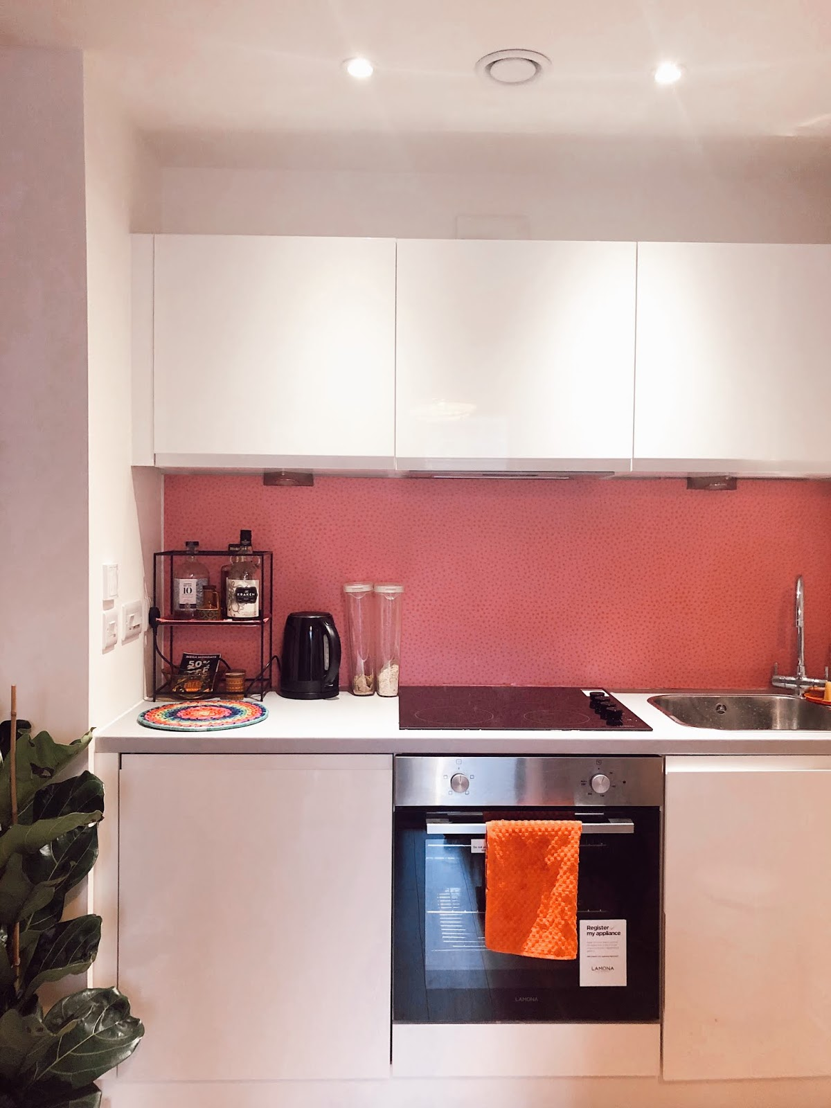 small modern white kitchen with pink spotty vinyl backsplash