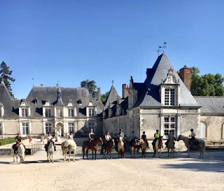 riders and horses standing in front of the Villesavin castle