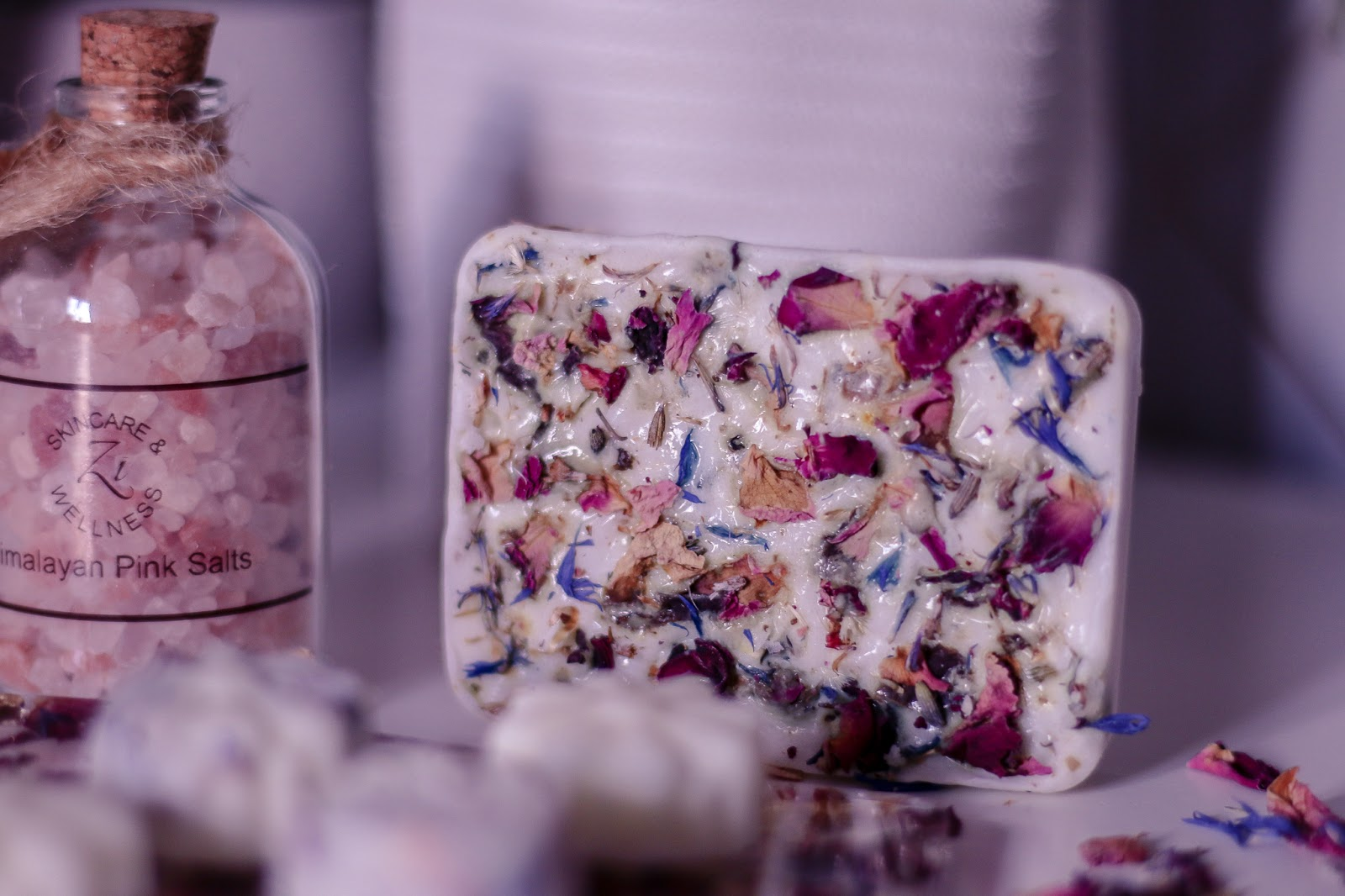 Close up of the white beauty bar with pink rose petals in it on a white bed side table