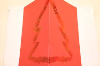Postal com contorno de árvore de Natal feito de glitter, em cartolina vermelha