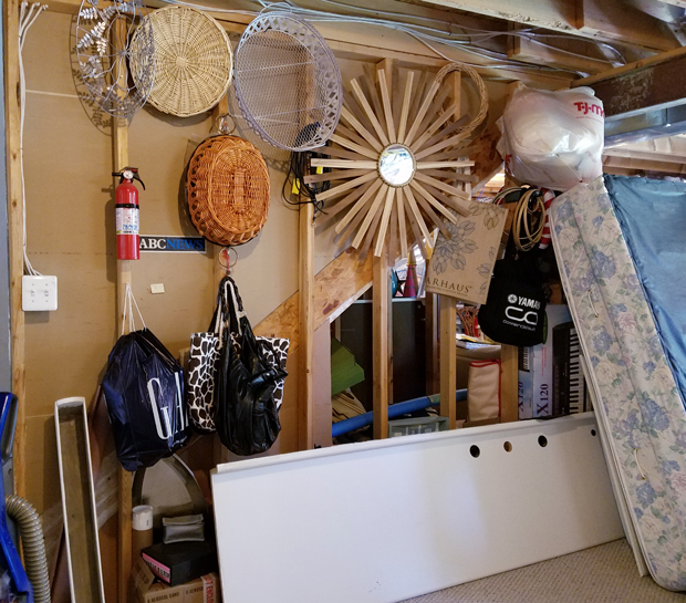 unfinished wall with exposed 2 x 4s, mattress standing up, stuff hung on 2x4s, baskets, mirror