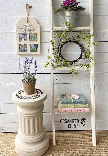 Photo of terracotta column pedestal staged with books, ladder, photo collage, and potted lavender