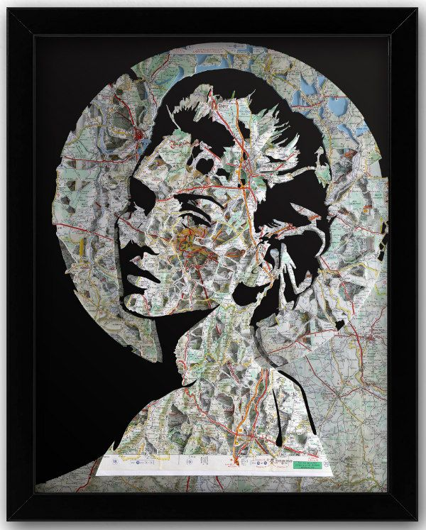 woman's head composed of paper cut layers of old maps in black frame