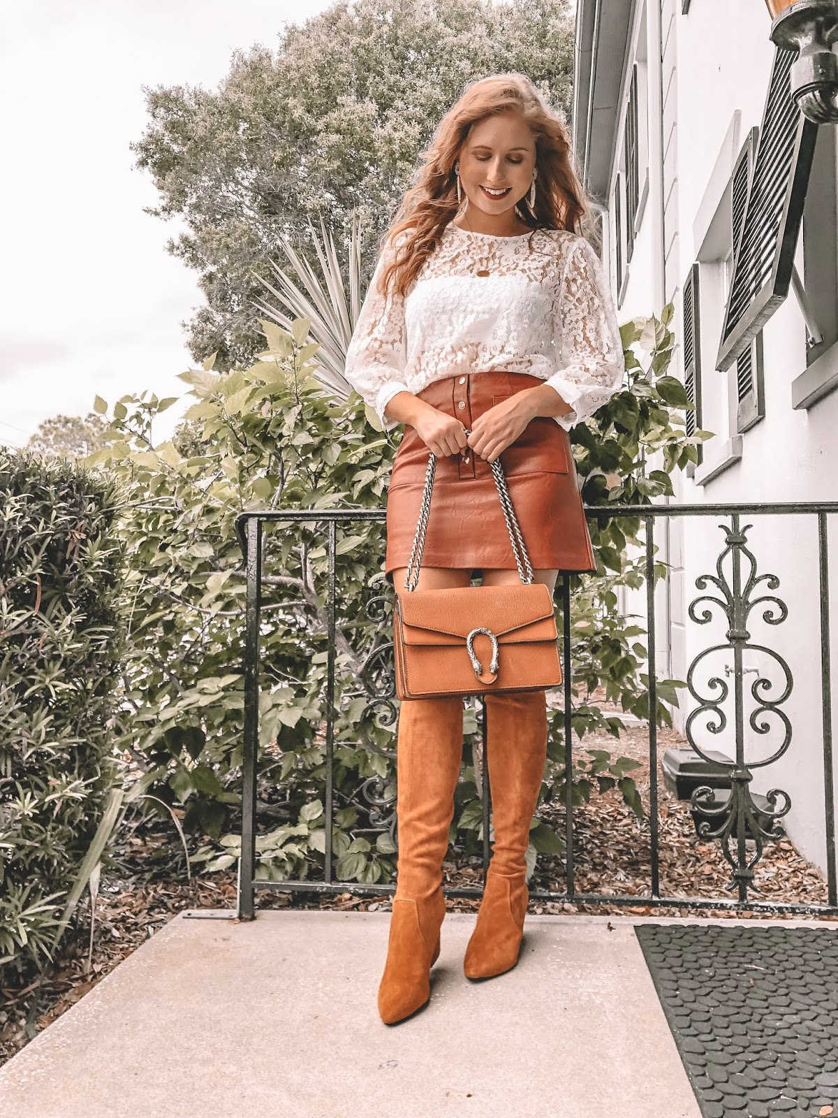 Tampa blogger Amanda Burrows is wearing a red leather skirt from Forever 21 with a long sleeve lace top. She is holding a Gucci shoulder bag in her hands.