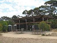 Campground facilities on the Kangaroo Island Wilderness Trail are good. Each campground has a communal kitchen and dining shelter like this one, with 4 picnic tables, a dishes and food prep area and filtered water.