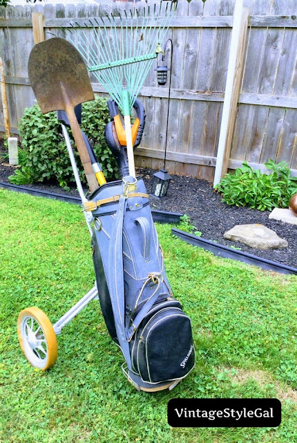 Golf bag in caddie with yard tools stored inside