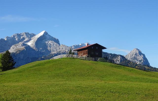 Eckbauer Alm auf grünem Hügel vor Wettersteingebirge, Zugspitze, Alpspitze