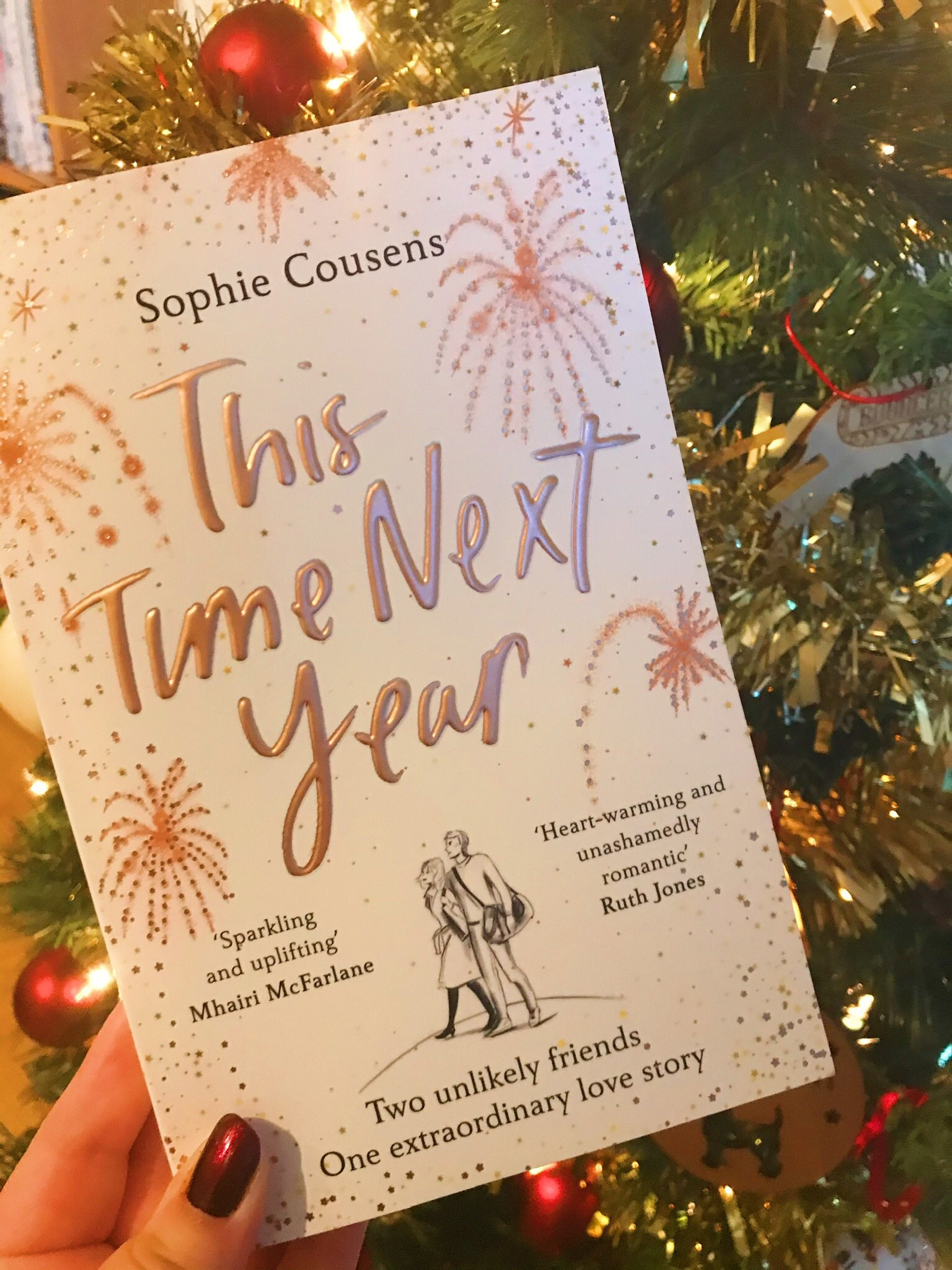 This Time Next Year by Sophie Cousens held up in front of Christmas tree