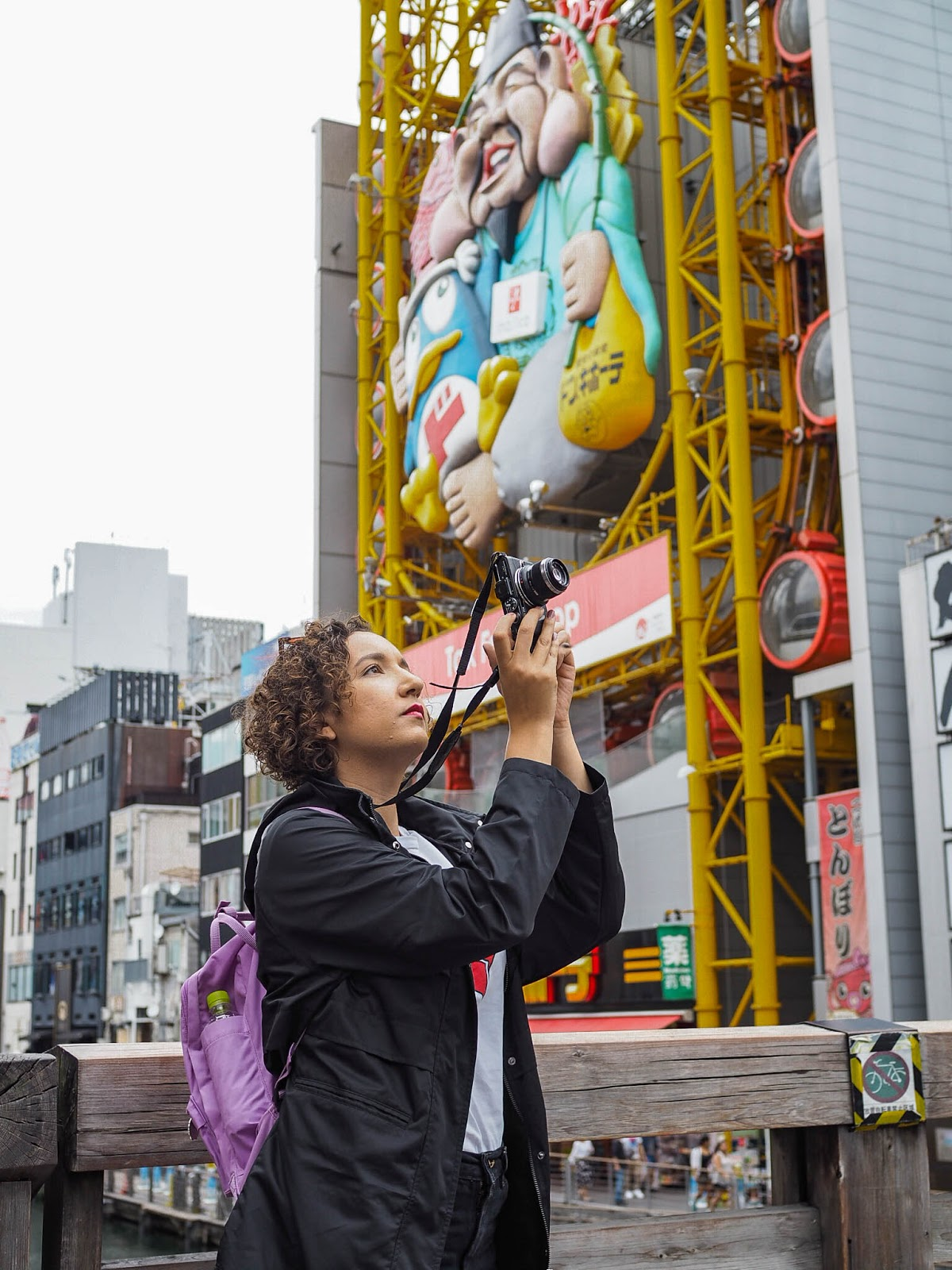 Taking a photo on the bridge over Dotonbori canal in Osaka