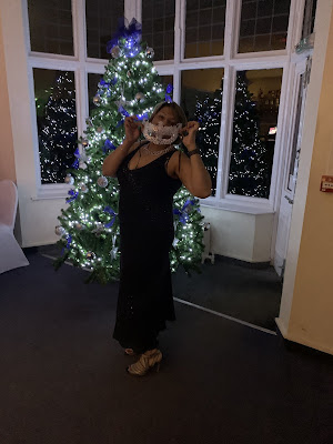 Woman standing in front of Christmas tree wearing a black dress and holding up a sequins mask to her face